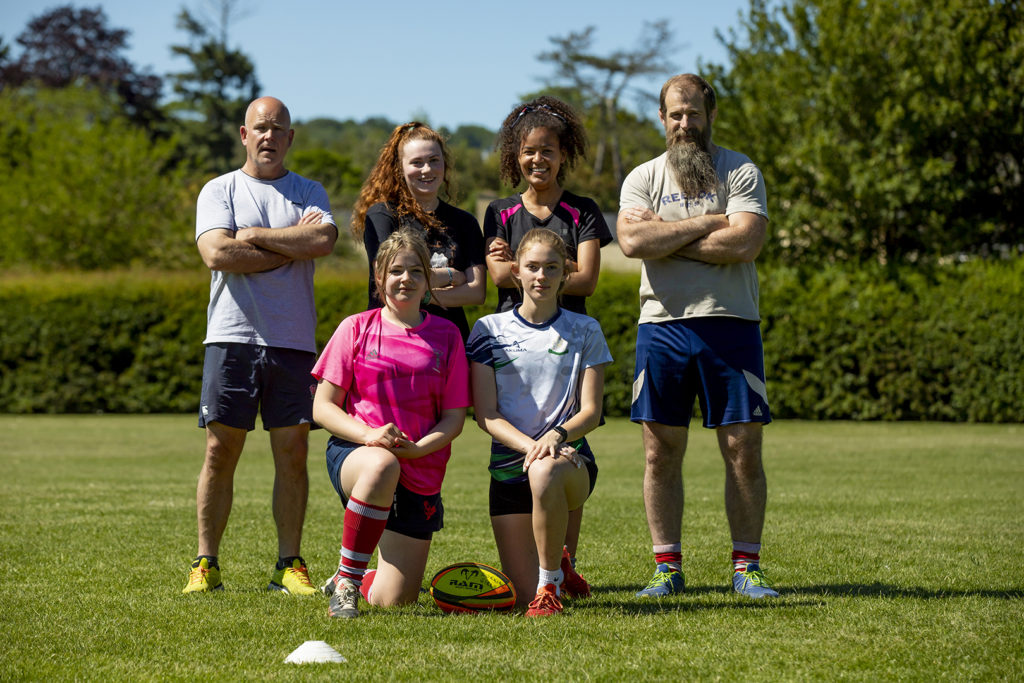 Women's rugby players with coaches